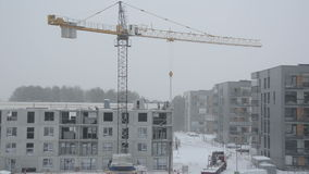 Dramatic snow fall and construction site workers builders work stock footage
