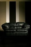 Dramatic sofa. Leather couch with dramatic lighting stock image
