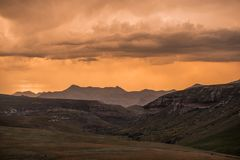 Dramatic storm clouds glow gold at sunset over the Drakensberg mountains surrounding the Amphitheatre, seen from Golden Gate stock images