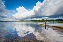 Dramatic storm clouds over a dock in Massabesic Lake, in Auburn,. New Hampshire royalty free stock image