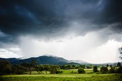 Dramatic storm clouds with rain. On mountain royalty free stock photo