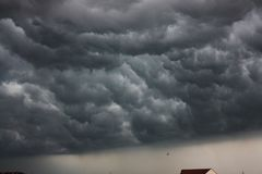 Dramatic, stormy clouds over the house roof. Dramatic, dark, stormy clouds over the house roof. Beginning of the storm Stock Image