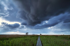 Dramatic stormy clouds over pier path Royalty Free Stock Images