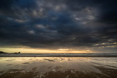 Dramatic stormy sky landscape reflected in low tide water on Rho. Dramatic stormy sky landscape reflected in low tide water on beach Rhosilli Bay Stock Photos