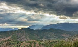 Dramatic stormy sky with sun rays through the clouds over a hilly valley. With mountains in the distance stock image