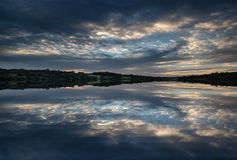 Dramatic stormy sunset over calm lake in Summer in English count Stock Photography