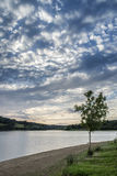 Dramatic stormy sunset over calm lake in Summer in English count Royalty Free Stock Photography
