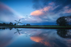 Dramatic stormy sunset over windmill by river Stock Image