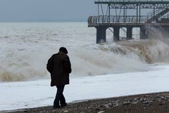 Dramatic, stormy weather, lonely old man walking along coast royalty free stock image