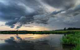 Dramatic summer sunset at the lake with dark clouds Stock Photo