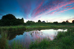 Dramatic summer sunset over rural lake. In Dutch farmland Royalty Free Stock Photography