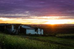 Summer sunset over humble farm and shack during peak harvest royalty free stock photo