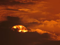Dramatic Sun partially hidden behind the Cloud at evening time with telephoto lens Royalty Free Stock Photo