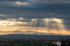 Free Dramatic Sun Ray Through Low Clouds Over City At Sunset. The Sun Cuts Through The Clouds Over The City. Sunbeams On The City Royalty Free Stock Images - 177496789