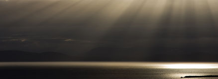 Dramatic Sunbeams. Against a stormy sky touch the ocean and distant islands Stock Photo
