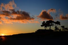 Dramatic sunrise colours; beautiful sunrise on a beach. Silhouettes of trees and buildings against colourful sky. Sky in the early sunrise; wonderful colours on stock photography