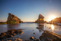 Dramatic sunrise with mist on the beach with rocks Stock Images