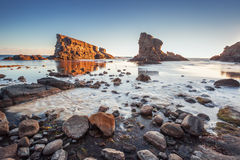 Dramatic sunrise with mist on the beach with rocks Stock Image
