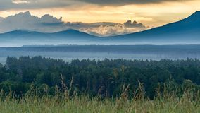 Dramatic sunrise in the mountains with thick evergreen forest in foreground covered with fog, Altai Mountains, Kazakhstan.  Royalty Free Stock Photography