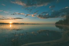 Dramatic sunrise over the calm river - vintage effect. Dramatic sunrise over the calm river in spring. Daugava, Latvia - vintage effect Stock Images