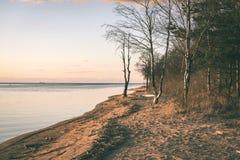 Dramatic sunrise over the calm river - vintage effect. Dramatic sunrise over the calm river in spring. Daugava, Latvia - vintage effect Royalty Free Stock Photos