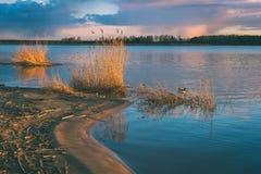 Dramatic sunrise over the calm river - vintage effect. Dramatic sunrise over the calm river in spring. Daugava, Latvia - vintage effect Stock Photos