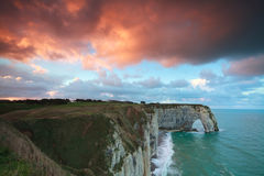 Dramatic sunrise over cliff in ocean Royalty Free Stock Photos