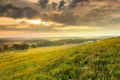 Dramatic Sunrise over the Kansas Tallgrass Prairie. A light fog and heavy dew fills the valley as this warm sunrise warms the sky on a mild summer morning in the stock images