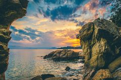 Dramatic sunrise over the sea framed by rocks Stock Images