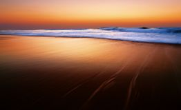 Dramatic sunrise or sunset at the Indian ocean. Durban, South Africa. Slow shutter used to show movement in waves and create a soft feel to image Royalty Free Stock Photography