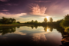 Dramatic sunrise on tranquil lake with reflections trees Royalty Free Stock Photo