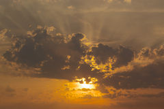 Dramatic sunset. Dramatic orange sunset with sunbeams coming through  stormy clouds, horizontal Royalty Free Stock Images