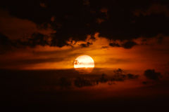 Dramatic sunset. Dramatic orange sunset with big sun covered by dark stormy clouds Stock Images