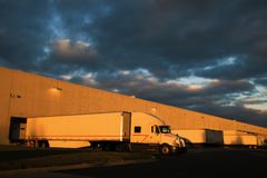 Dramatic sunset above distribution warehouse. Semi Truck ready to leave royalty free stock photography