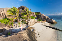 Dramatic sunset at Anse Source d`Argent beach, La Digue island, Seychelles. Female traveler emjoying climbing ob beautifully shaped granite boulders at picture Royalty Free Stock Photography