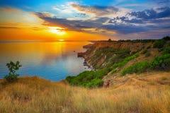 Dramatic sunset at cape fiolent. Crimea. Dramatic sunset at cape fiolent with bush and grass at foreground. Crimea Royalty Free Stock Photo