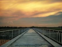Dramatic sunset clouds at the end of the bridge royalty free stock photography