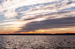 Dramatic sunset with cloudy sky, lake landscape Stock Photo