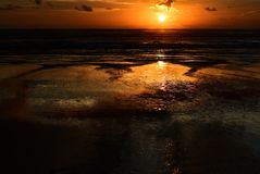 Dramatic sunset colours; beautiful sunset on a beach. Sun reflection in the water. stock photos