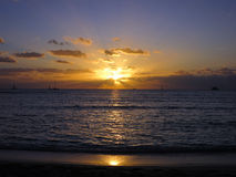 Dramatic Sunset dropping behind the ocean shining over boats. On Waikiki Beach on Oahu, Hawaii Stock Image