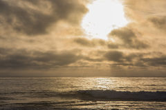 Dramatic sunset with god rays on pacific ocean beach Stock Photo
