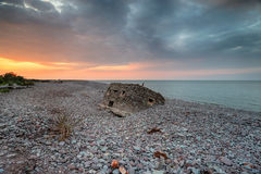 Dramatic Sunset over the Beach at Porlock Weir. Dramatic sunset over the ruins of an old World War 2 pillbox on the beach at Porlock Weir on the Exmoor coast in stock image