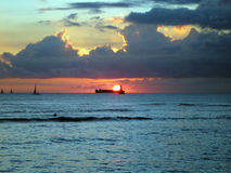 Dramatic Sunset over a cargo boat below the clouds and reflectin Royalty Free Stock Photography