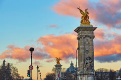 Dramatic sunset over the columns of Pont Alexandre III in Paris Stock Images