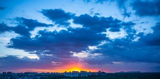 Dramatic sunset over evening city with bright blue clouds and sky, beautiful panorama. Dramatic sunset over evening city with bright blue clouds and sky royalty free stock photo