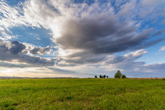 Dramatic sunset over green field.  Stock Image