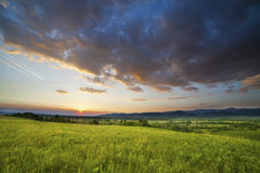 Dramatic sunset over green field Stock Photo