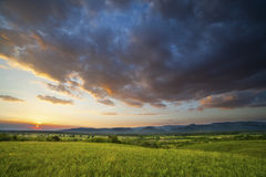 Dramatic sunset over green field Royalty Free Stock Photos