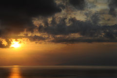 Dramatic sunset over La Gomera island from Tenerife, Canary Islands. Horizontal shot of sun casting golden rays upon the ocean, forming a path of light and soft stock image