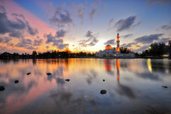 Dramatic sunset over the mosque with sky reflections on water Stock Image